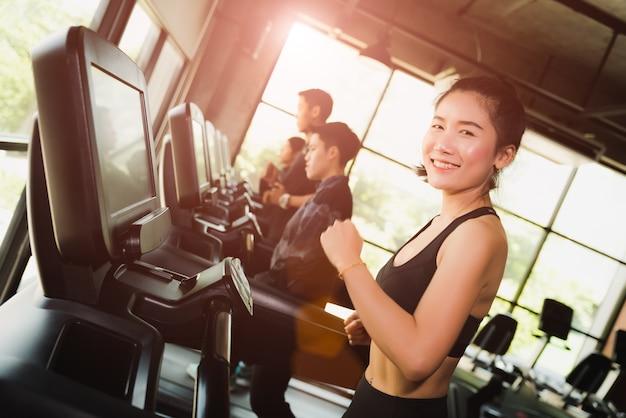 Kobieta bieganie lub jogging na bieżni w nowoczesny sport siłownia. koncepcja ćwiczeń.