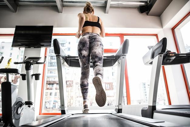 Kobieta biegnie na bieżni w jasnej sali gimnastycznej.