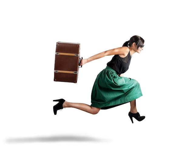 Kobieta biegnie z walizką