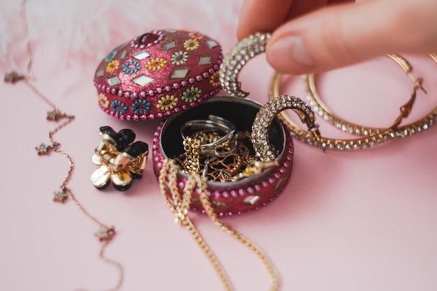 Kobieta bierze biżuterię z małego pudełeczka na różowym tle