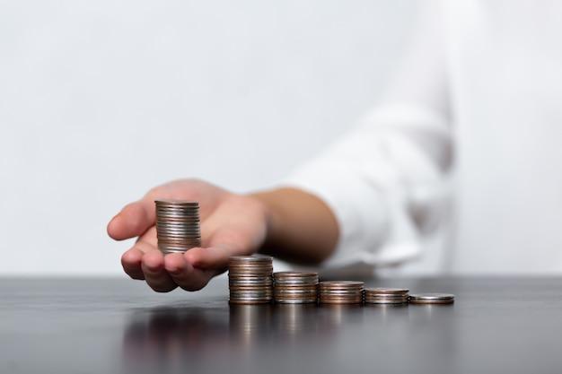 Kobieta bierze do ręki stos monet z kilku stosów monet. pojęcie oszczędzania pieniędzy, polityki finansowej i inwestycyjnej. przykład podatków od ludności.