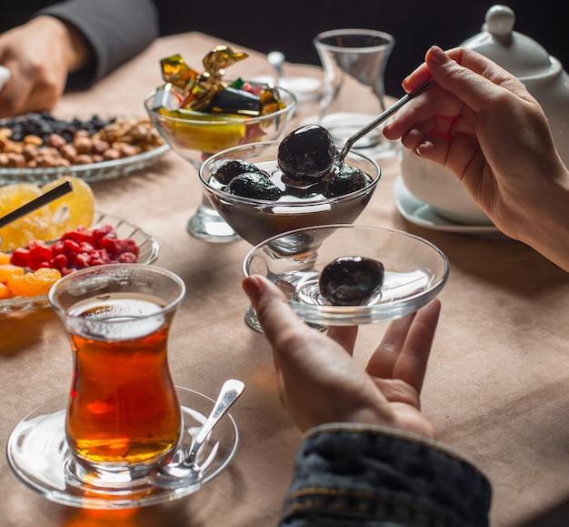 Kobieta bierze dżem orzechowy z kryształowej miski ze stojakiem w siedzeniu herbaty