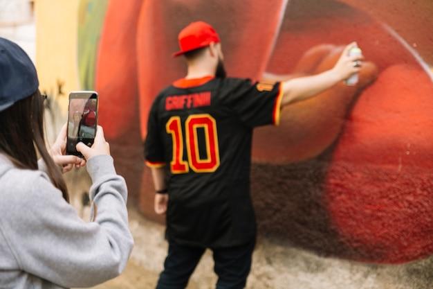 Kobieta bierze fotografię mężczyzna opryskiwanie na graffiti ścianie