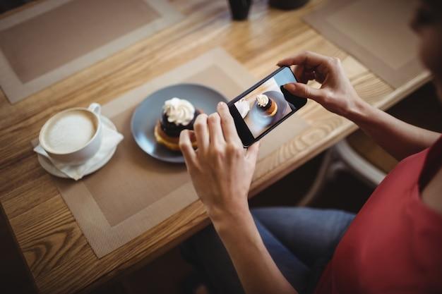 Kobieta bierze fotografię słodki jedzenie od telefonu komórkowego