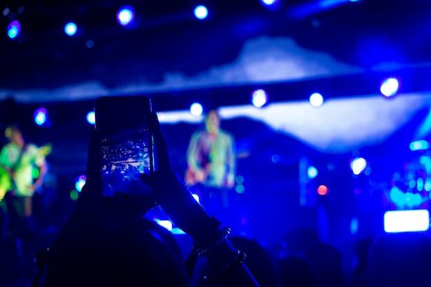 Kobieta bierze fotografię z telefonem przy muzycznym wydarzeniem