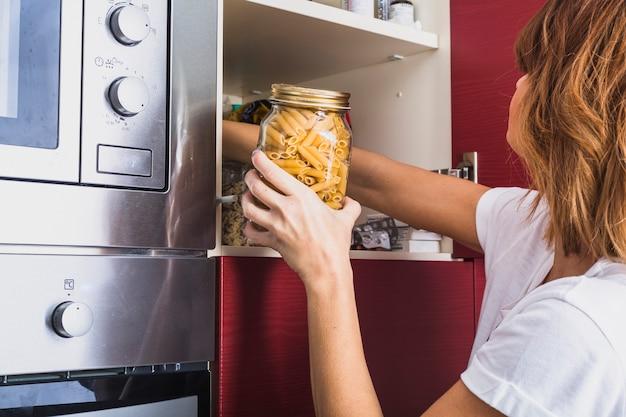 Kobieta bierze kulinarnych składniki od szafki