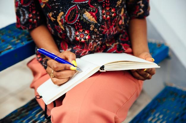 Kobieta bierze notatki w notatniku, siedzi na schodkach, outdoors. ubrany w kolorowe ubrania.