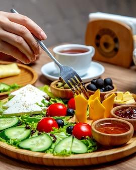 Kobieta bierze plasterek sera cheddaru słuzyć w śniadaniowym półmisku