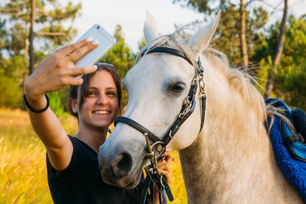 Kobieta bierze selfie z białym koniem w wsi