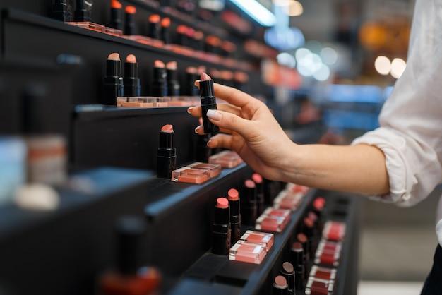 Kobieta bierze szminkę z półki w sklepie kosmetycznym. kupujący na wystawie w luksusowym salonie kosmetycznym, klientka na rynku mody