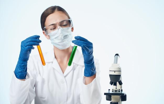 Kobieta biolog w medycznych rękawiczkach mikroskop szczepień na stole badawczym w pierwiastku chemicznym.