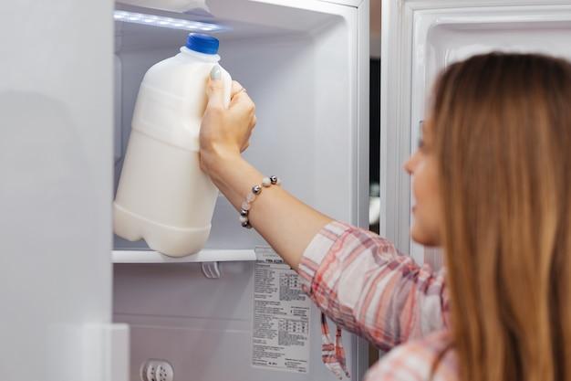 Kobieta biorąc jedzenie z lodówki z bliska zdjęcie