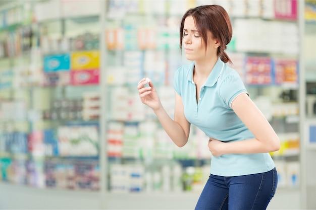 Kobieta biorąc tabletkę. zbliżenie dłoni z pigułką i ustami, na białym tle