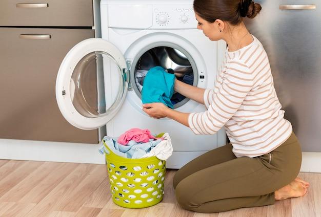 Kobieta biorąc ubrania z pralki