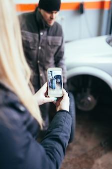 Kobieta biorąc zdjęcie mechanik samochodowy naprawy jej samochodu.