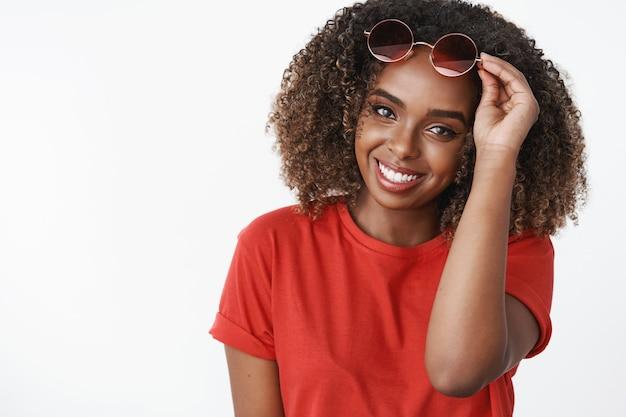 Kobieta biorąca okulary przeciwsłoneczne rozmawiająca z uroczym facetem podchodząca na powitanie uśmiechnięta zalotna i urocza z przodu trzymająca okulary na czole ubrana w czerwoną koszulkę czująca czułość i optymizm na białej ścianie