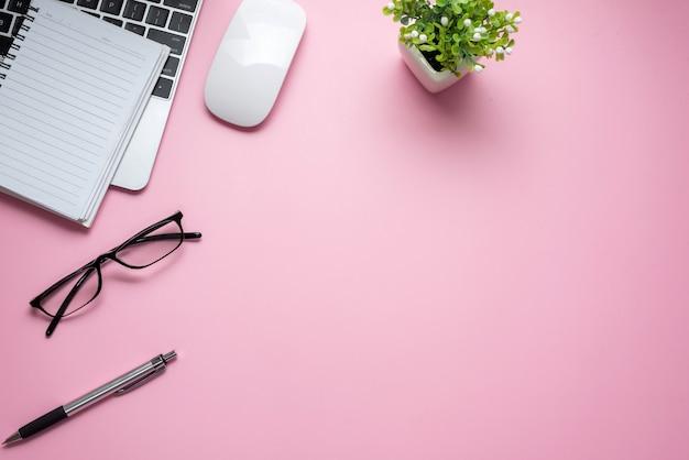Kobieta biurko z klawiaturą notebook okulary pióro mysz widok z góry różowy stół. skopiuj miejsce.