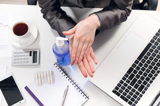 Kobieta biznesmen lub menedżer dezynfekuje ręce przy pomocy antybakteryjnego środka przeciwbakteryjnego na biurku