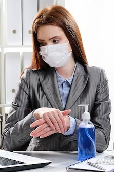Kobieta biznesmen w masce medycznej dezynfekuje ręce przy biurku przy użyciu antybakteryjnego środka na bazie alkoholu