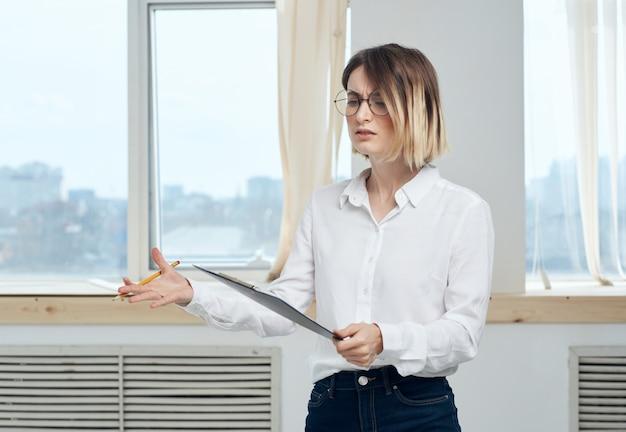 Kobieta biznesu, ale jesteśmy z białą kartką papieru w pobliżu okna
