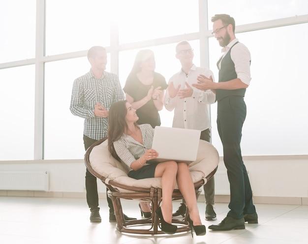 Kobieta biznesu i jej zespół biznesowy są w miejscu pracy w biurze. ludzie i technologia