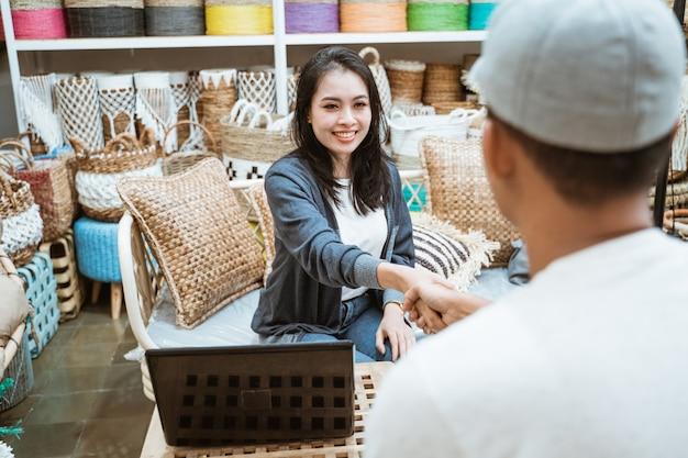 Kobieta biznesu i klient zawierają umowę, ściskając ręce nad laptopem w galeriach rzemieślniczych