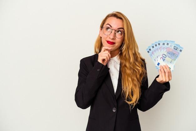 Kobieta biznesu kaukaski gospodarstwa rachunki na białym tle patrząc w bok z wyrazem wątpliwości i sceptyczny.