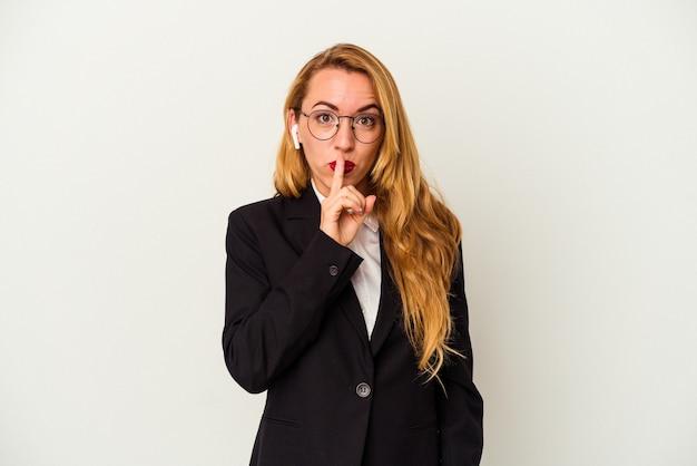Kobieta biznesu kaukaski nosi bezprzewodowe słuchawki na białym tle dochowując tajemnicy lub prosząc o ciszę.