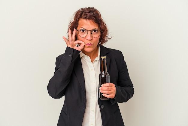 Kobieta biznesu łacińskiego wieku średniego trzyma piwo na białym tle z palcami na ustach dochowując tajemnicy.