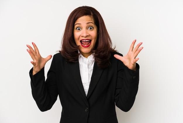 Kobieta biznesu łacińskiej średnim wieku na białym tle świętuje zwycięstwo lub sukces, jest zaskoczony i zszokowany.