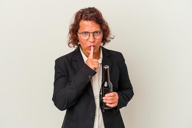 Kobieta biznesu latynoski w średnim wieku trzymając piwo na białym tle dochowując tajemnicy lub prosząc o ciszę.