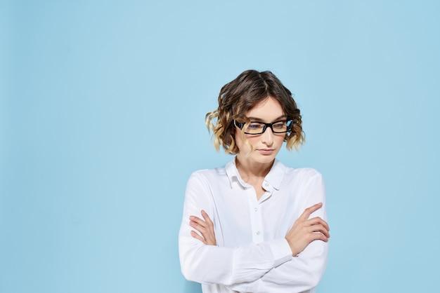 Kobieta biznesu na niebieskich okularach z ciemnymi obrzeżami kręconych włosów jasna koszula przycięty widok.