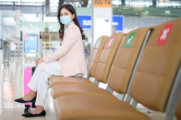 Kobieta biznesu nosi maskę ochronną na lotnisku międzynarodowym, podróżuje w czasie pandemii covid-19,