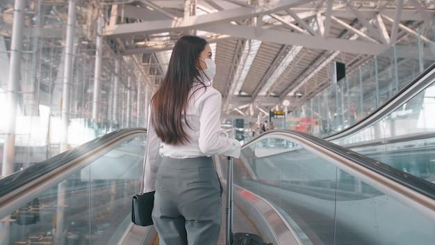 Kobieta biznesu nosi maskę ochronną na lotnisku międzynarodowym, podróżuje w czasie pandemii covid-19