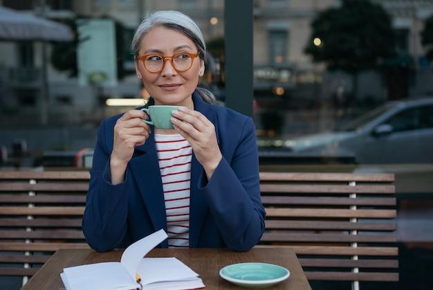 Kobieta biznesu obornika picia kawy w kawiarni