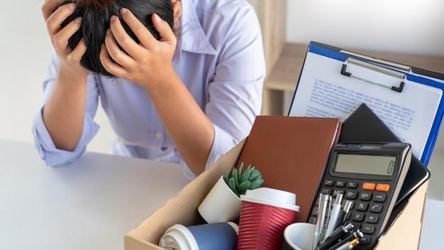 Kobieta biznesu pakująca brązowe kartonowe pudełko jej przynależności po rezygnacji i podpisaniu listu anulującego umowę