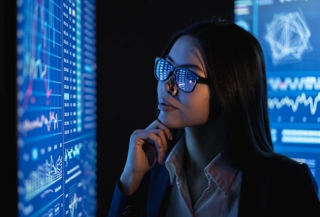 Kobieta biznesu patrzy na duży niebieski ekran z wykresem