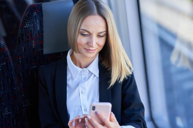 Kobieta biznesu podmiejskiego metra w transporcie publicznym za pomocą smartfona