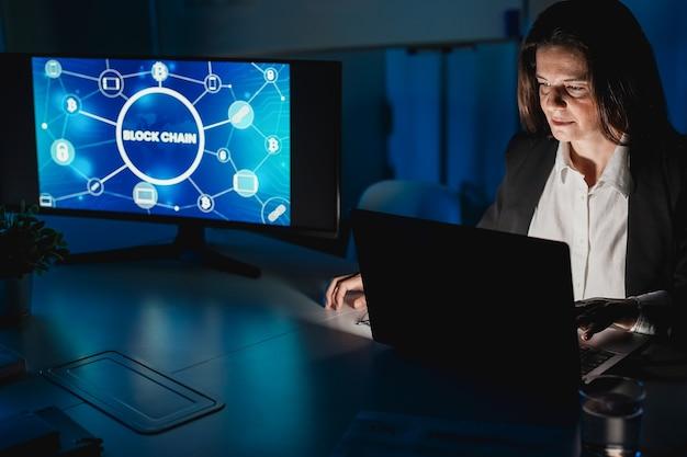 Kobieta biznesu przeprowadzająca badania nad blockchainem, pracująca w nocy w biurze firmy fintech - skup się na twarzy