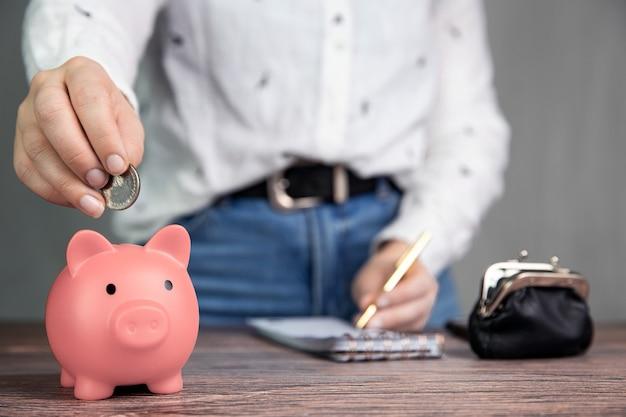 Kobieta biznesu robi administrację, liczy i oszczędza pieniądze z różową skarbonką