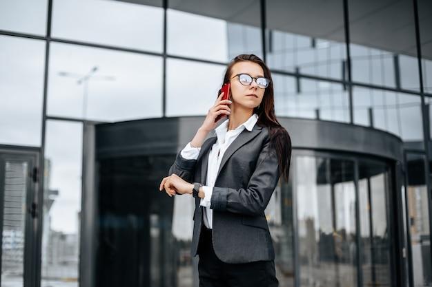 Kobieta biznesu sprawdza godzinę i rozmawia przez telefon w mieście w ciągu dnia roboczego w oczekiwaniu na spotkanie. dyscyplina i wyczucie czasu. pracownik udaje się na spotkanie firmowe.