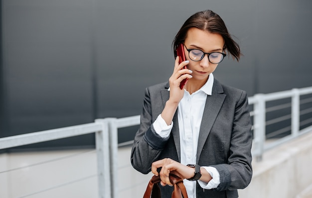 Kobieta biznesu sprawdza godzinę w mieście podczas dnia roboczego, czekając na spotkanie. dyscyplina i czas. pracownik idzie na spotkanie firmowe.