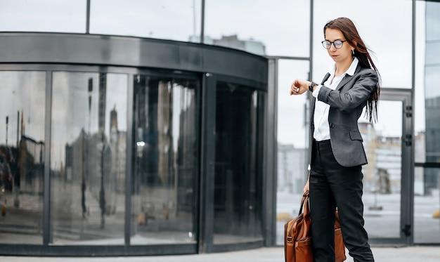 Kobieta biznesu sprawdza godzinę w mieście w dzień roboczy czekając na spotkanie. dyscyplina i wyczucie czasu. pracownik udaje się na spotkanie firmowe.