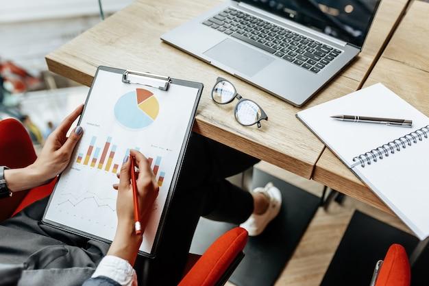 Kobieta biznesu sprawdza wykresy i odświeża postęp finansowy