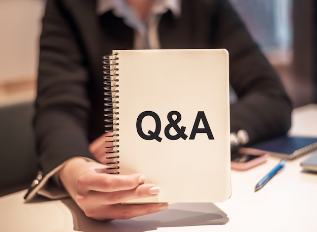 Kobieta biznesu trzyma notatnik z tekstem pytania i odpowiedzi