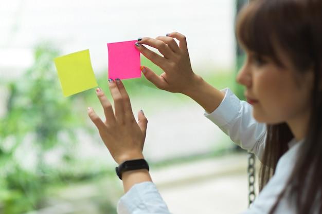 Kobieta biznesu używająca karteczek samoprzylepnych, aby podzielić się pomysłem kampanii marketingowej na szklanym oknie