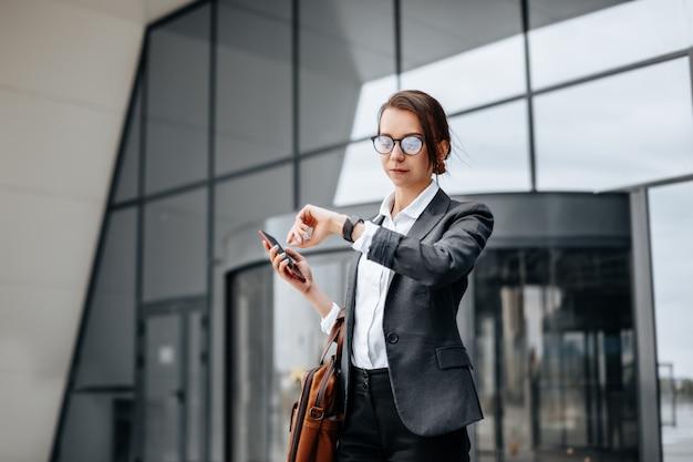 Kobieta biznesu w dniu roboczym w oczekiwaniu na spotkanie sprawdza godzinę w mieście