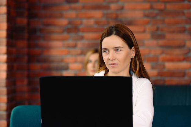 Kobieta biznesu w eleganckich strojach wizytowych, korzysta z laptopa i patrzy oczami w bok. nowe nowoczesne wnętrze z cegły w stylu loft.