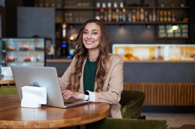 Kobieta biznesu właściciel restauracji użyj laptopa w rękach ubranych w elegancki kombinezon siedząc przy stole w restauracji z blatem barowym kaukaska kobieta biznesmena wewnątrz
