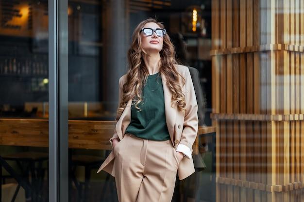 Kobieta biznesu właścicielka restauracji, ubrana w elegancki kombinezon stojący w pobliżu restauracji duże okno na zewnątrz kaukaskich kobiet okulary osoba biznesu